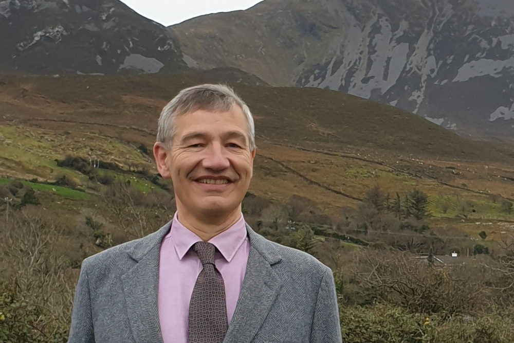 Man standing in front of mountains in Mayo.