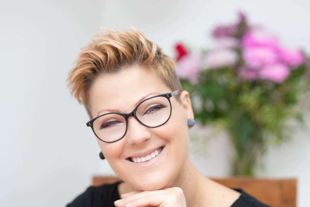 Smiling woman with blonde/red hair and glasses.