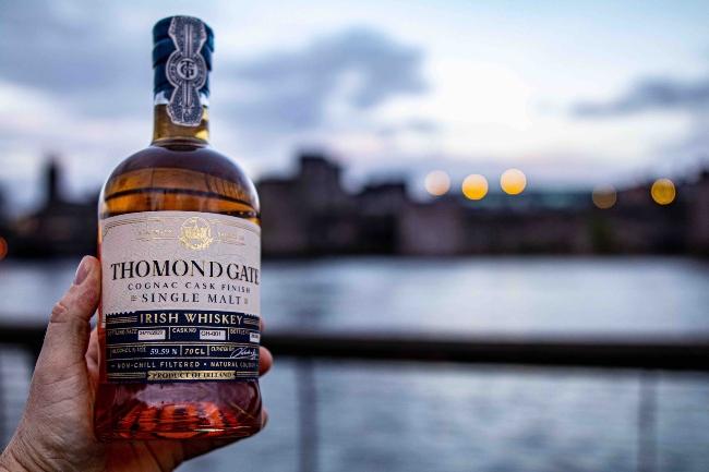 Holding a bottle of whiskey in front of King John's Castle in Limerick