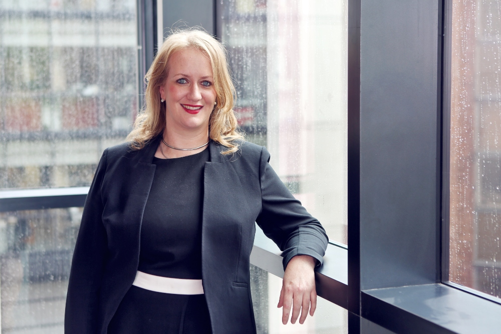 Blonde-haired woman in black business suit.