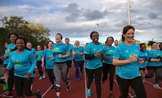 women in blue t-shirts at a running event.