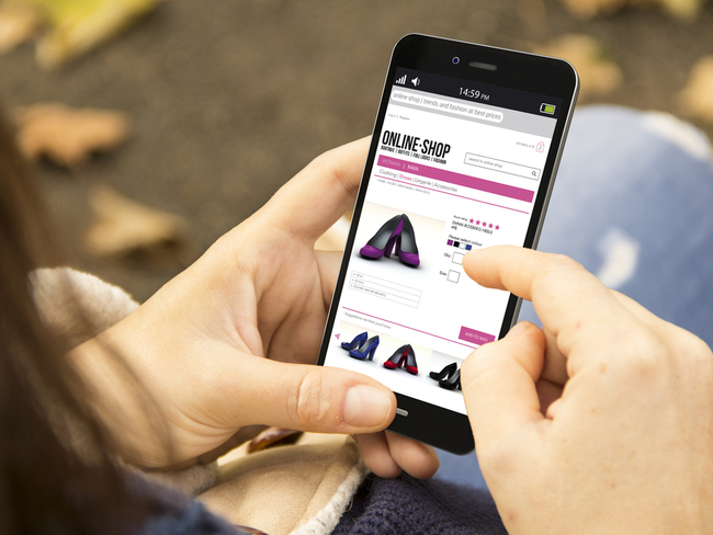 Woman looking at shoes on her smartphone.