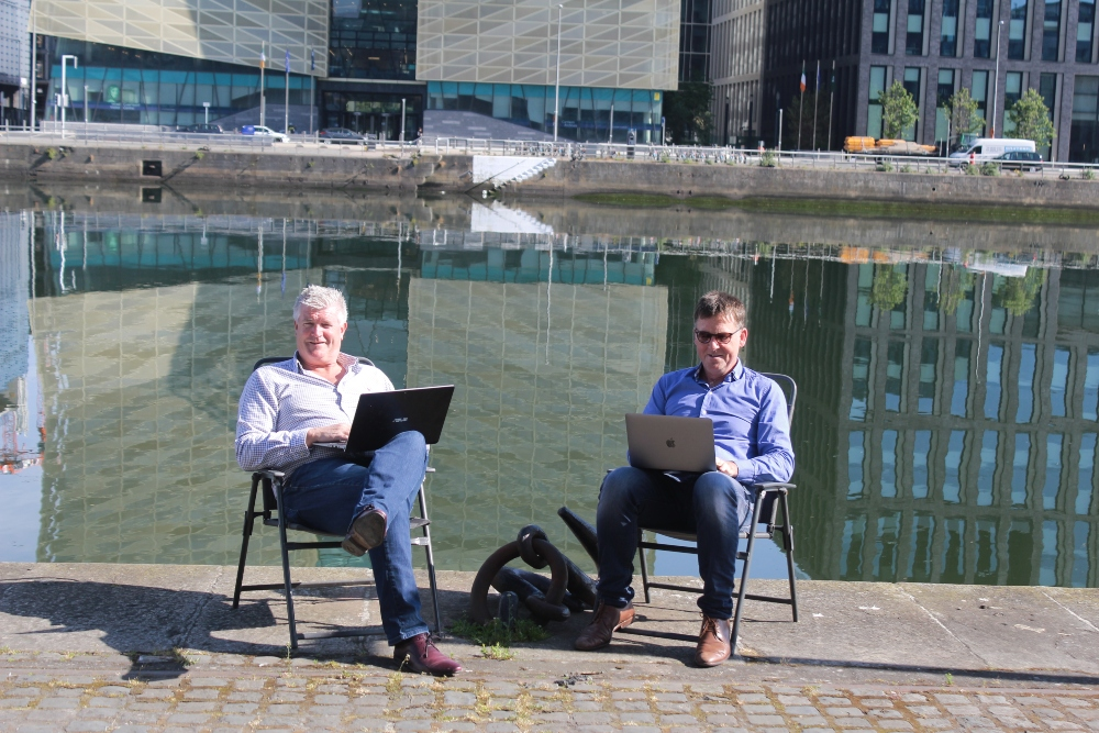 Two men with laptops sitting by the River Liffey.