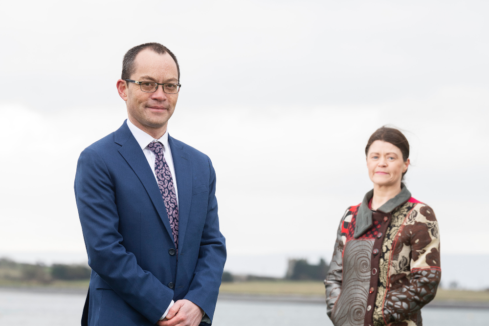 Man in suit and women in coat standing beside a bay.