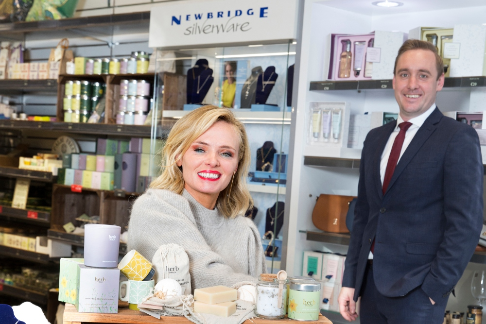 Blonde-haired woman in shop with suited man.