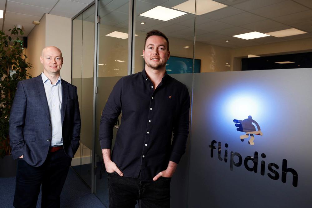 Two men standing beside Flipdish logo on glass window.