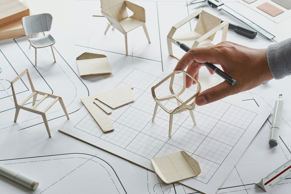 Designer with 3D printed models of chairs.