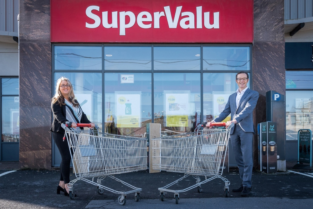 Woman and man standing outside SuperValu store with trolleys.