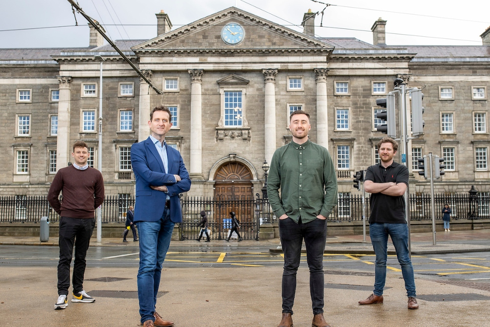 Four men standing in front of Trinity College.