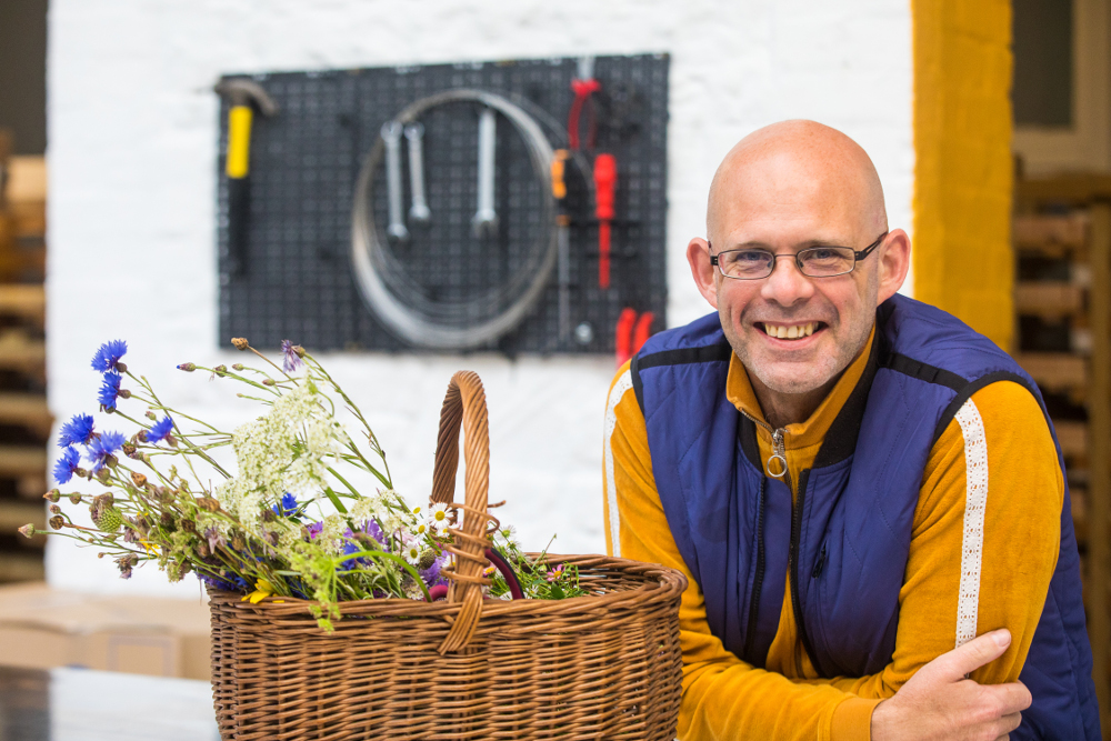 Smiling man beside a basket full of herbs and flowers.