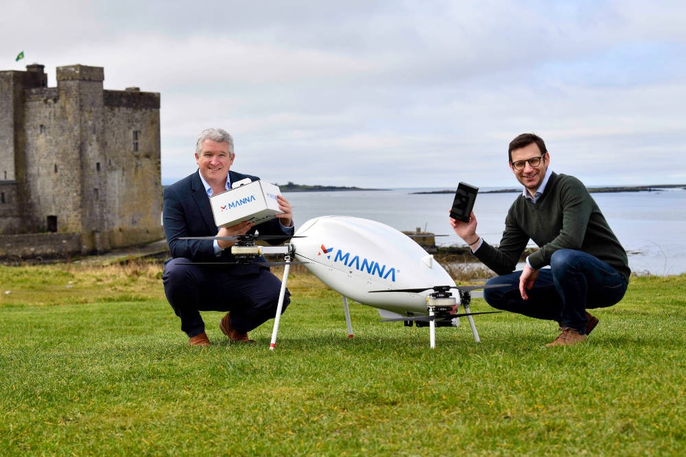 Two men with a large drone in front of an Irish castle.