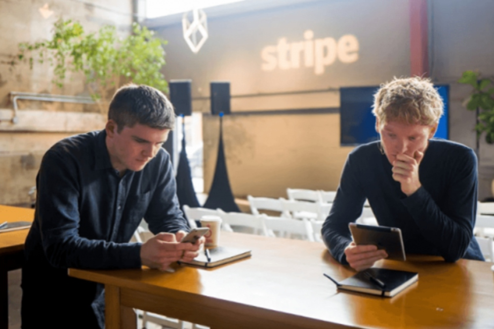 Two young founders of Stripe sitting at a table.