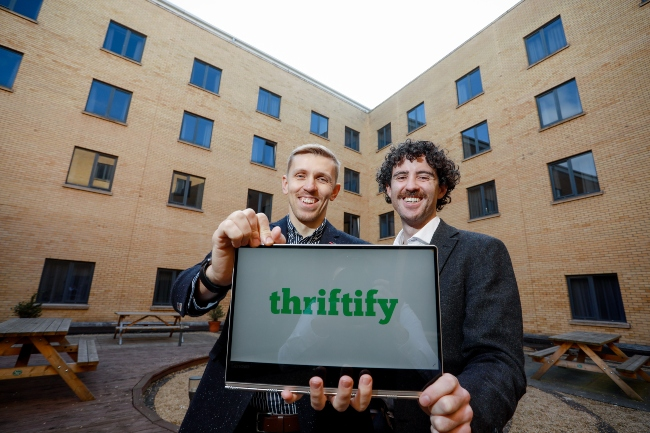 Two men holding a laptop that says Thriftify on the screen.