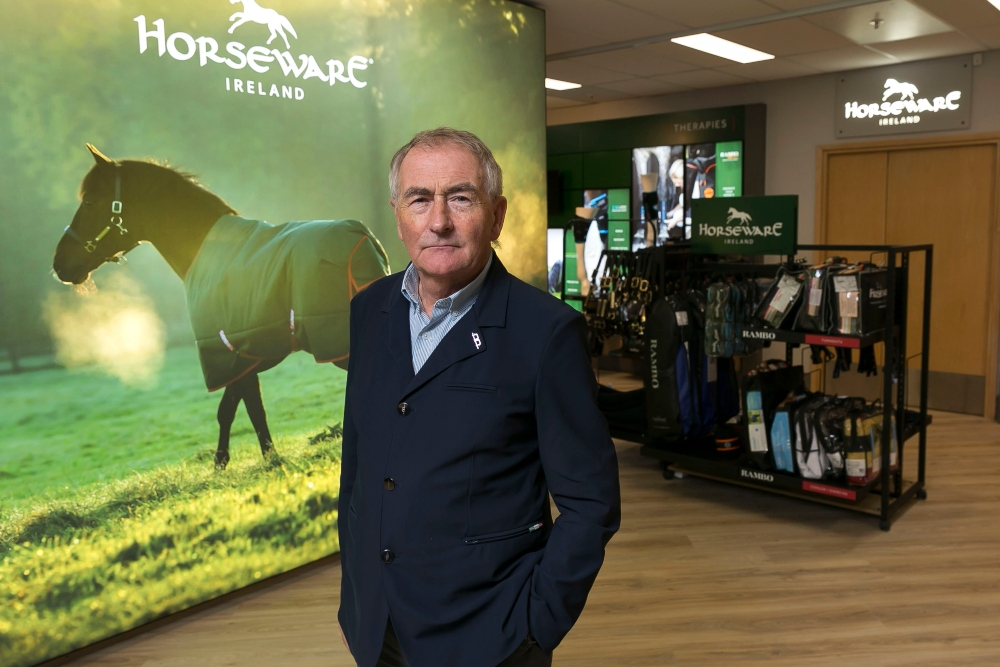 Man standing in a shop selling horse sports gear.