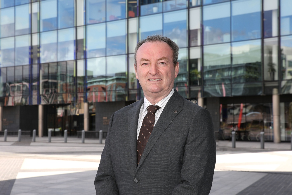Man in suit standing in front of glass buildings.