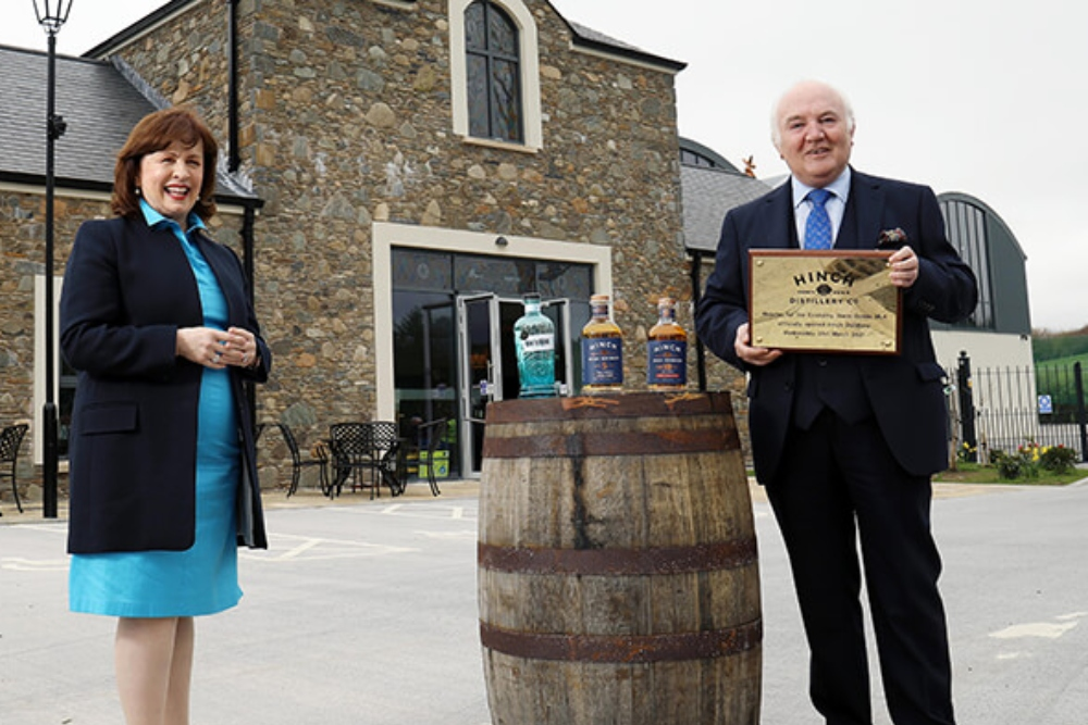 Man and woman standing in front of a distillery.