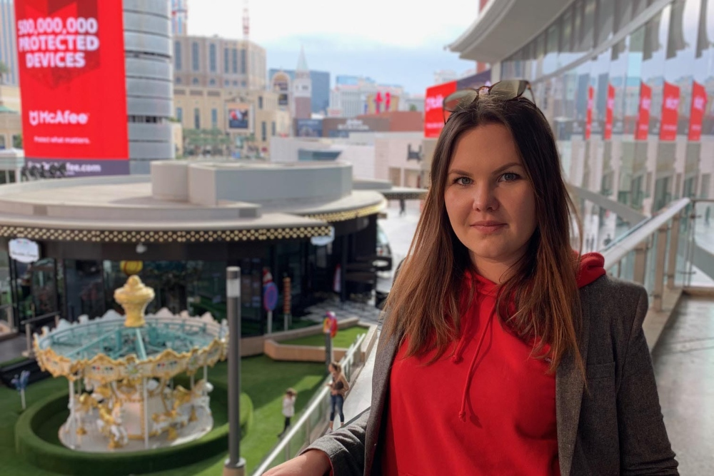 Brown haired woman in red top standing on a balcony at Mobile World Congress in Barcelona.