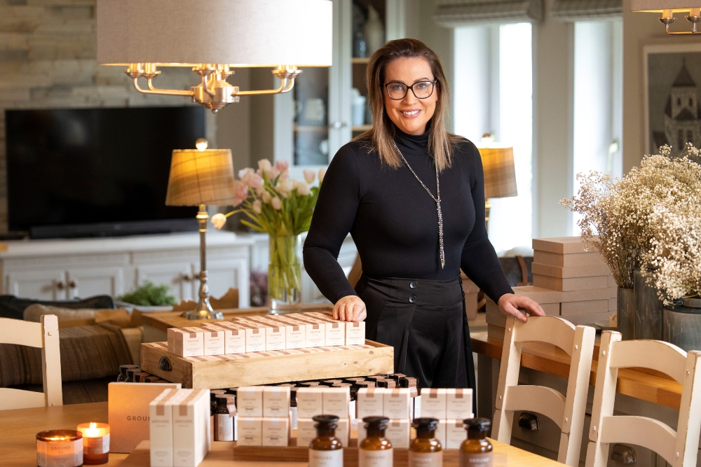 Woman with brown hair and glasses beside luxury oils and spa treatments.