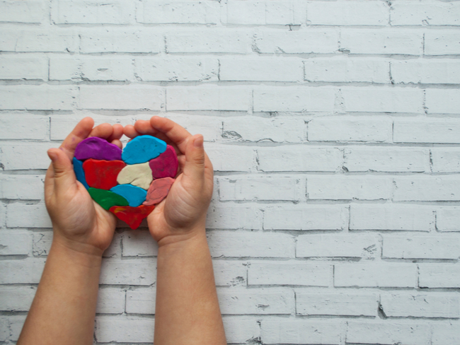 Child's hands holding a multicolored heart on white background.