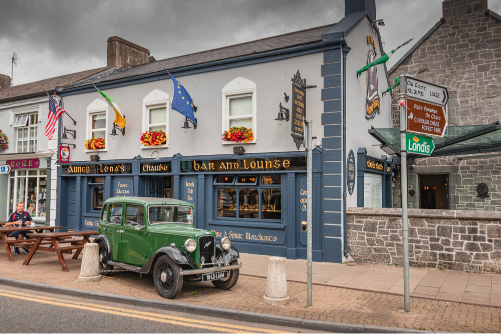 View of a typical Irish pub with the blue facade and vintage car in the town of Adare.