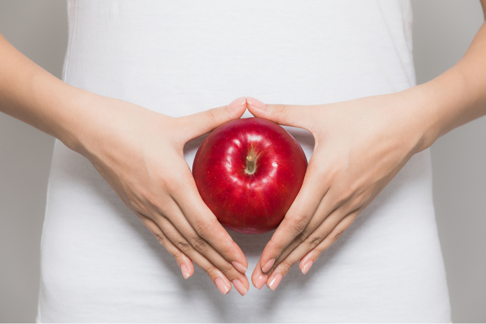 young woman holding an apple on her stomach.