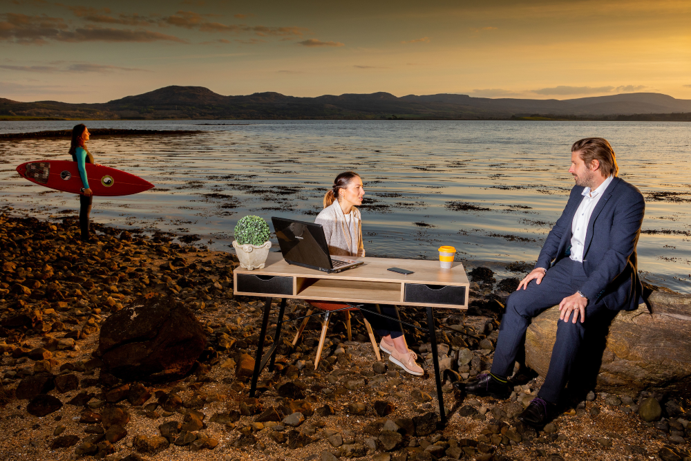 Woman with surf board on beach beside man and woman at office desk,