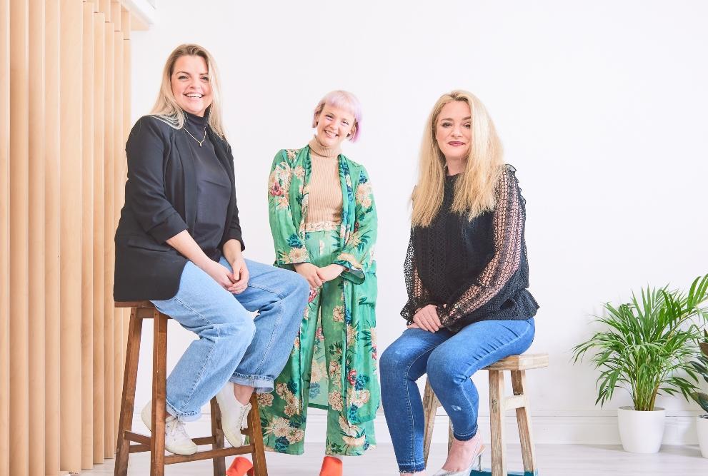 Three women sitting on stools.