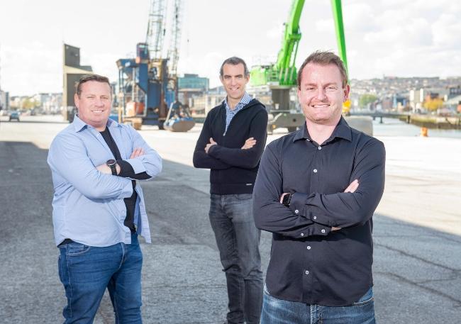 Three men standing at Cork harbour.