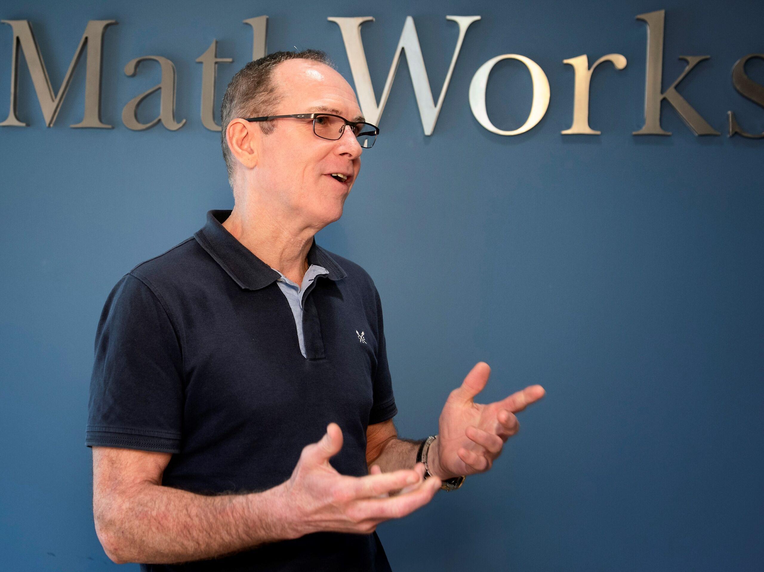Man in black t-shirt under a sign saying MathWorks.