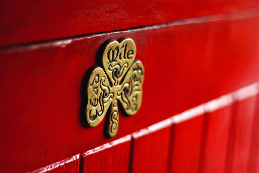Royalty-free stock photo ID: 1732860071 Irish phrase of welcome, Céad Míle Fáilte, A hudred thousand welcomes, written on a lucky shamrock plaque on a red door, Galway, Ireland.