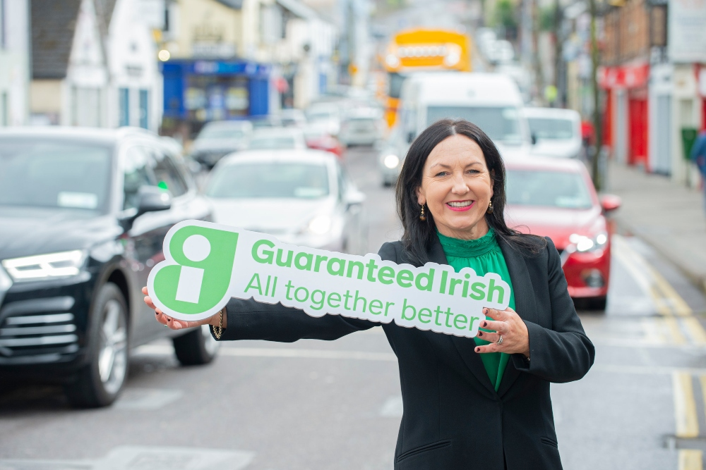 Woman in business suit holding a Guaranteed Irish symbol.