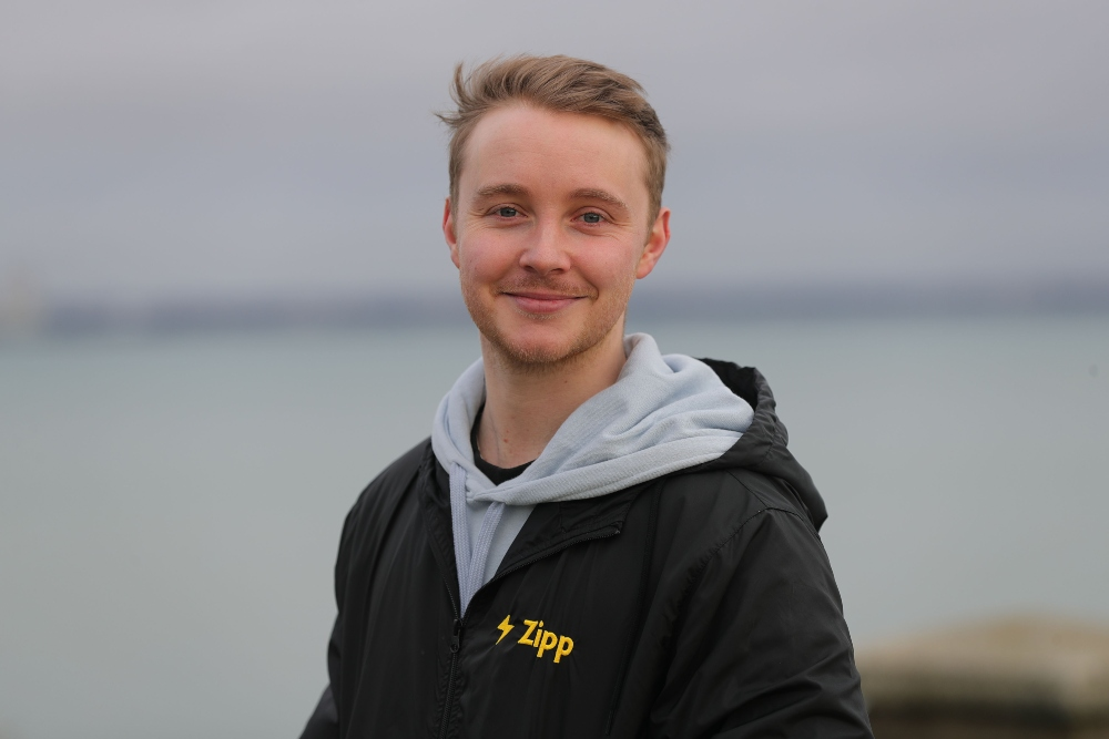 Young man in grey and black hoodie.