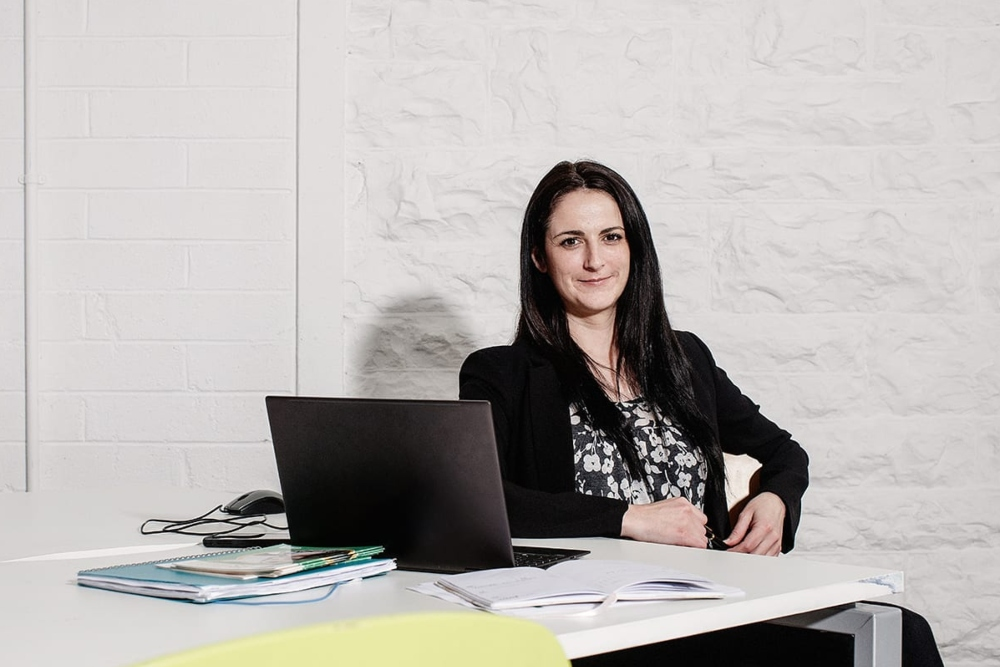 Young woman in black jacket sitting at a desk.