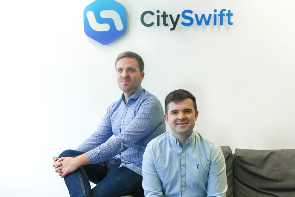 Two young executives in blue shirts sitting on a couch.