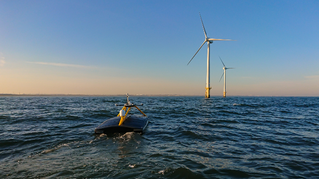 Robot boat approaching wind farm.