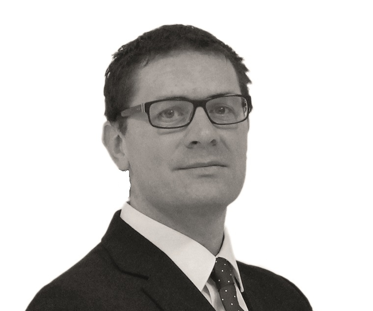 Man wearing glasses and suit.