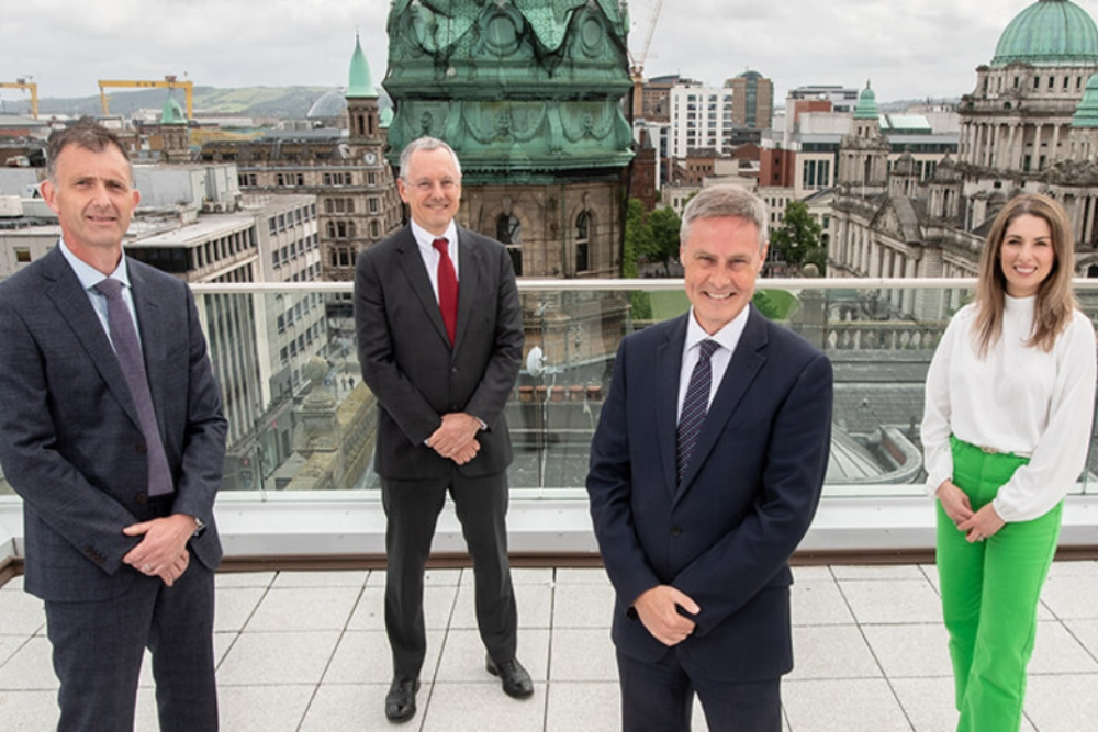 Three men and a woman standing on a roof in Belfast.