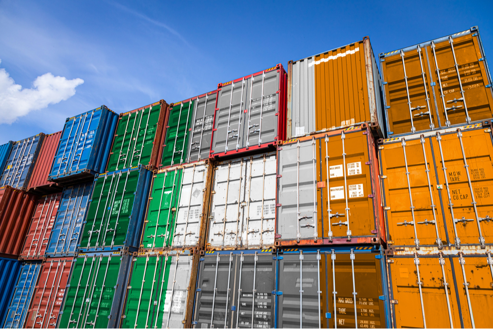 The national flag of Ireland on a large number of metal containers for storing goods stacked in rows on top of each other.