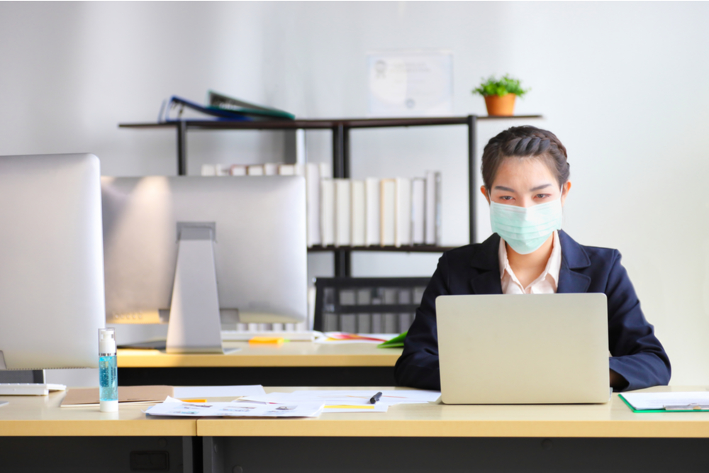 Female employee wearing medical facial mask working alone as of social distancing policy in the business office during new normal change after coronavirus or post covid-19 outbreak pandemic situation.