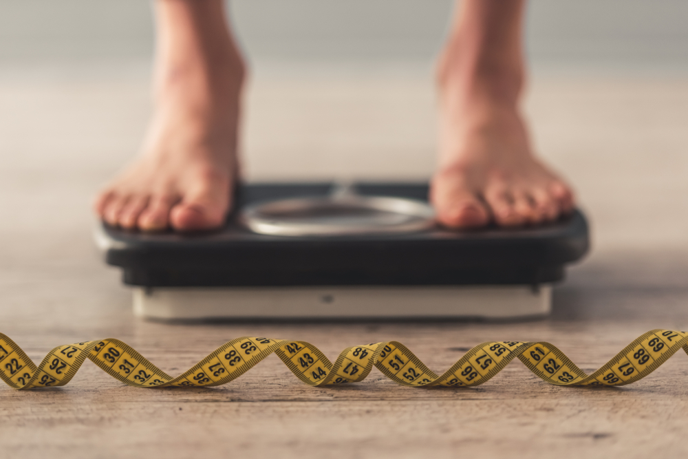 A person standing on a weighing scales.