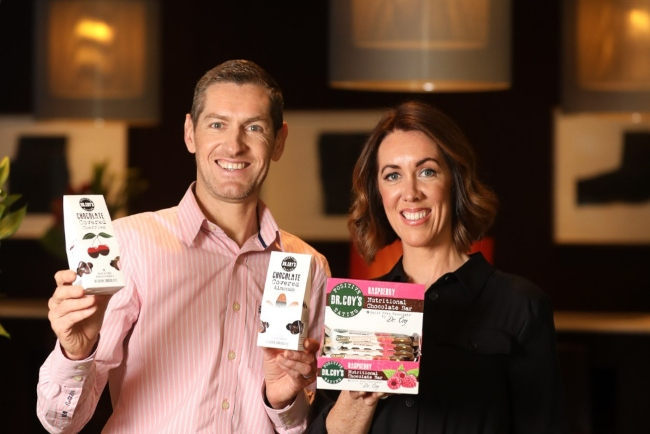 Man and woman holding chocolate products.