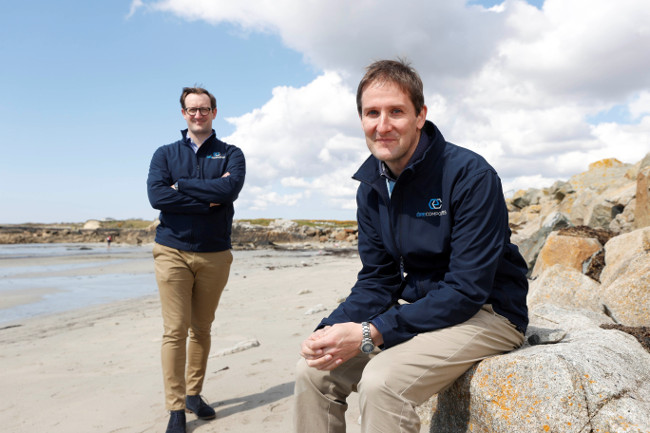 Two men sitting on a beach in Galway.