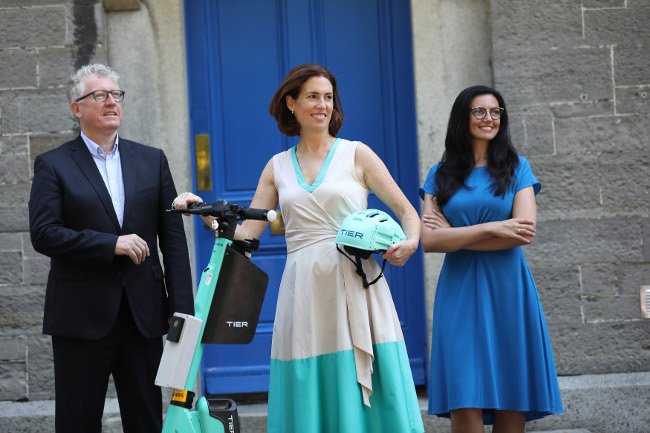Two women and a man with an e-scooter.