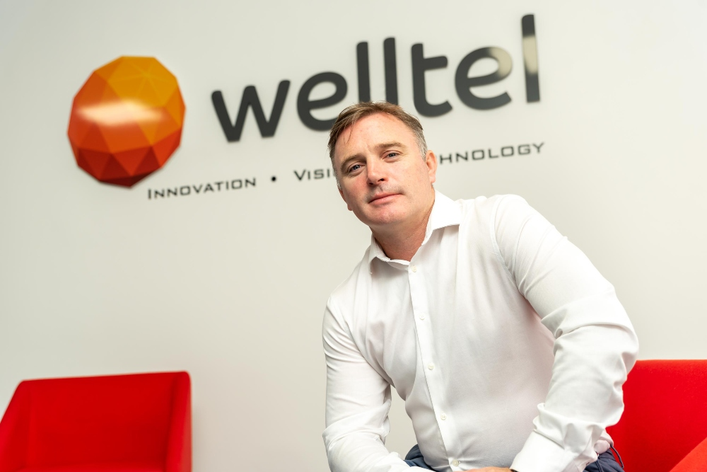 Business man in white shirt sitting under a sign saying Welltel.