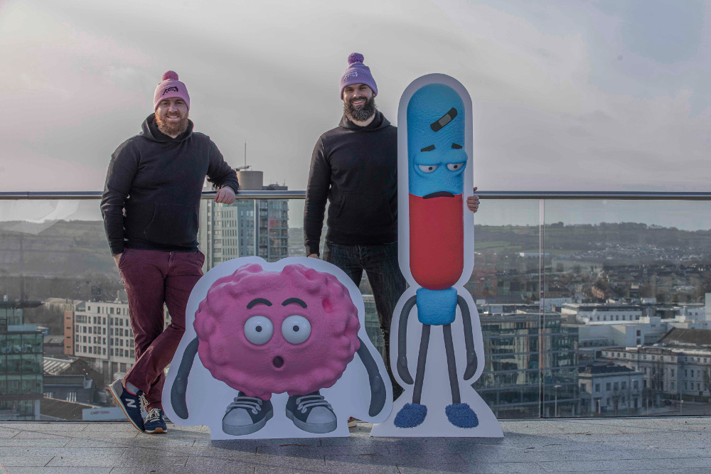 Two men on a rooftop in Cork with animated characters.