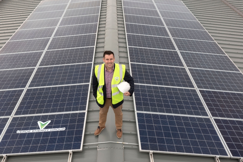 Man in hi-vis jacket standing on a roof full of solar panels.
