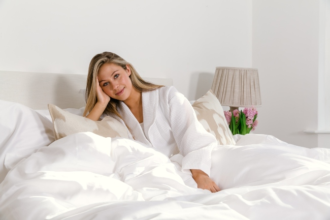 Woman relaxing on a bed with white sheets.