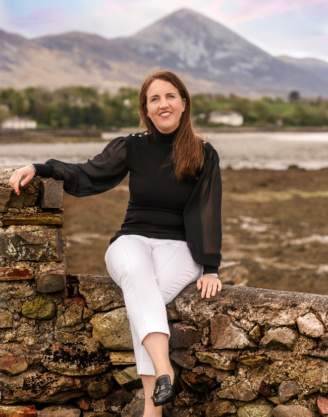Dakr-haired woman sitting in a wall in Mayo.