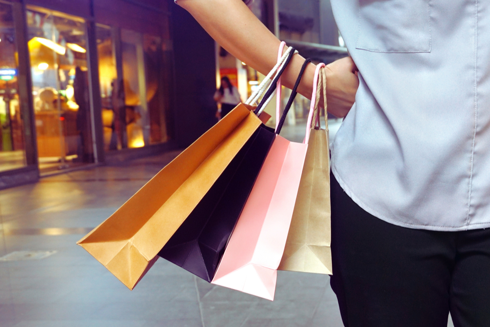 Woman hanging shopping bags in her hand and acting hands on waist.