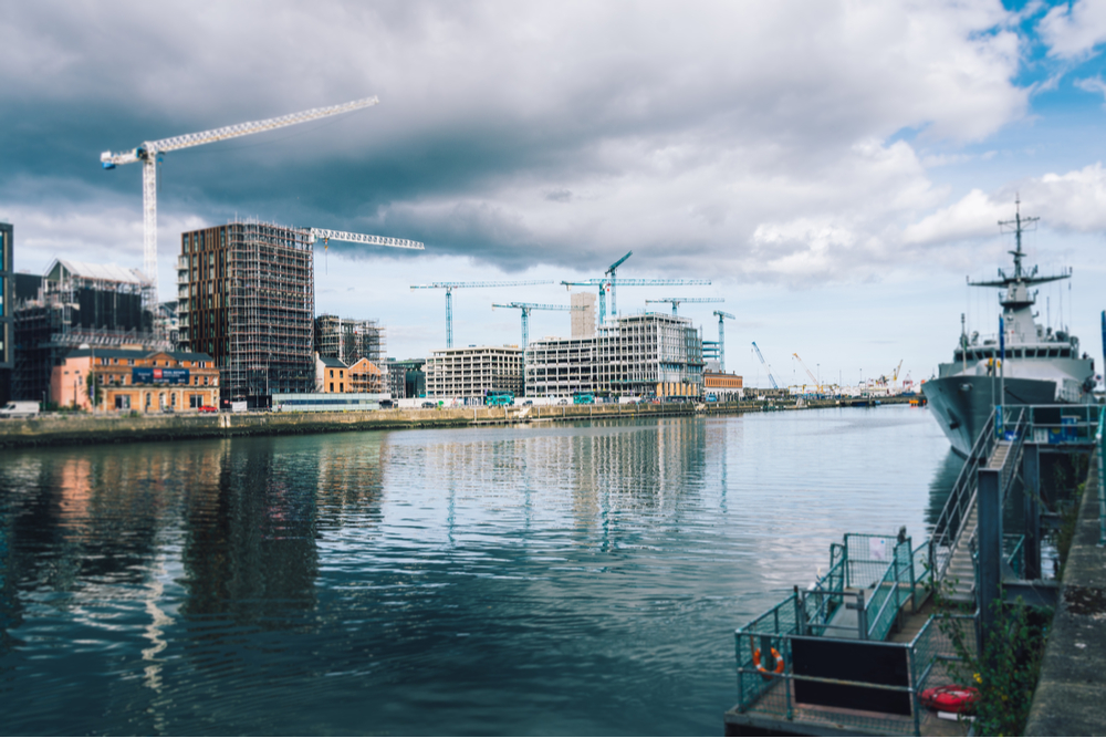 View of the Liffey river in Dublin showing city buildings in constructions and cranes.